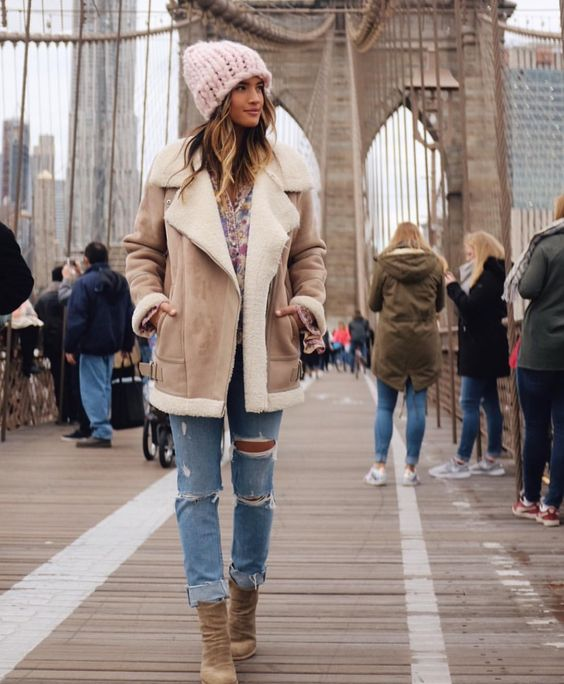 blue ripped denim, a floral shirt, neutral boots, a neutral shearling coat and a blush beanie