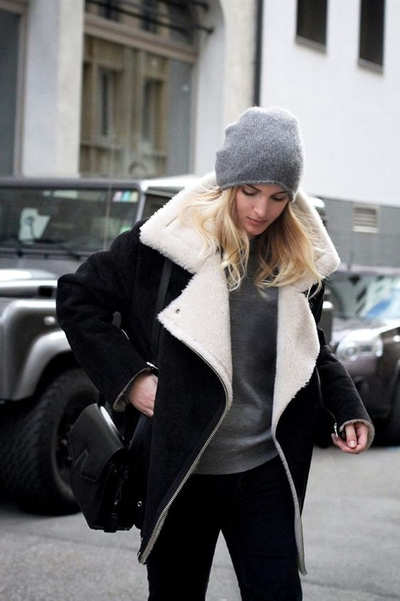 a casual look with black skinnies and a black shearling coat, a grey sweater and a beanie