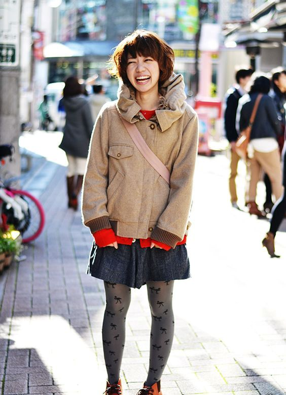 a red sweater, a grey mini skirt, a neutral coat, printed tights, orange shoes