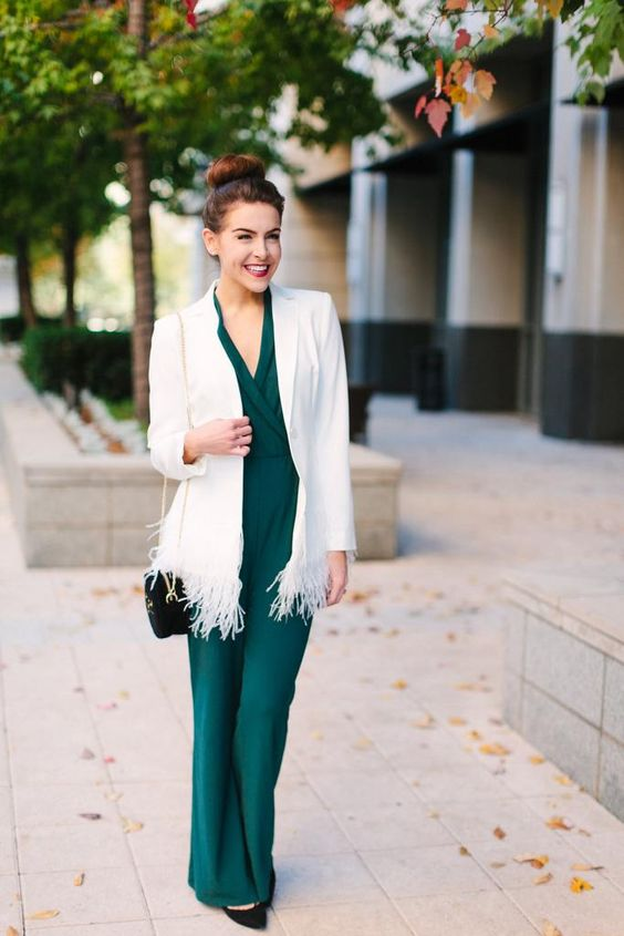 an emerald jumpsuit, a creamy long blazer with feathers, black pumps and a black bag
