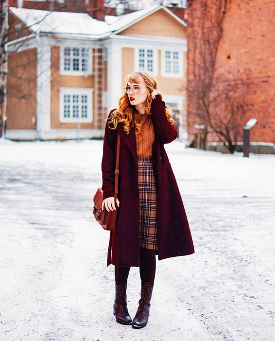 an orange sweater, a plaid knee skirt, burgundy tights, tall boots and a plum-colored coat and a rust bag