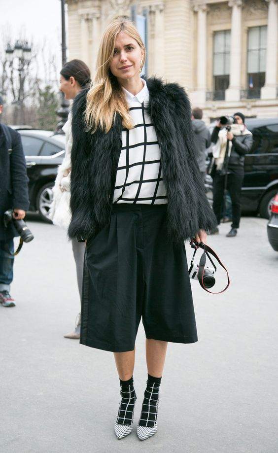 black culottes, a white shirt, a windowpane sweater, matching socks, polka dot shoes and a black fuzzy coat