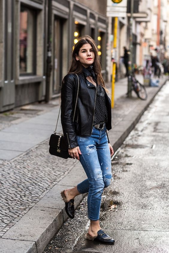 a black printed shirt, a black leather jacket, blue ripped jeans and fur loafers