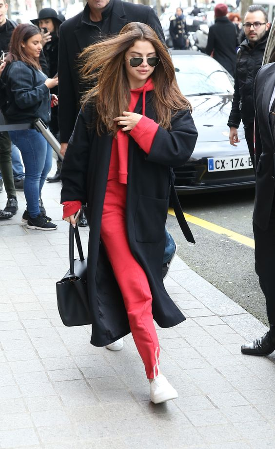 a red tracksuit, white sneakers, a black coat and a bag by Selena Gomez