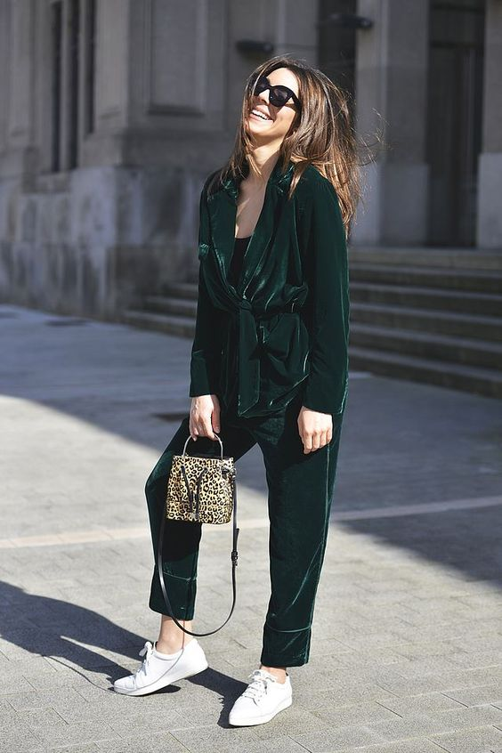 a street style outfit with an emerald oversized pantsuit, a black top, white sneakers and an animal print bag
