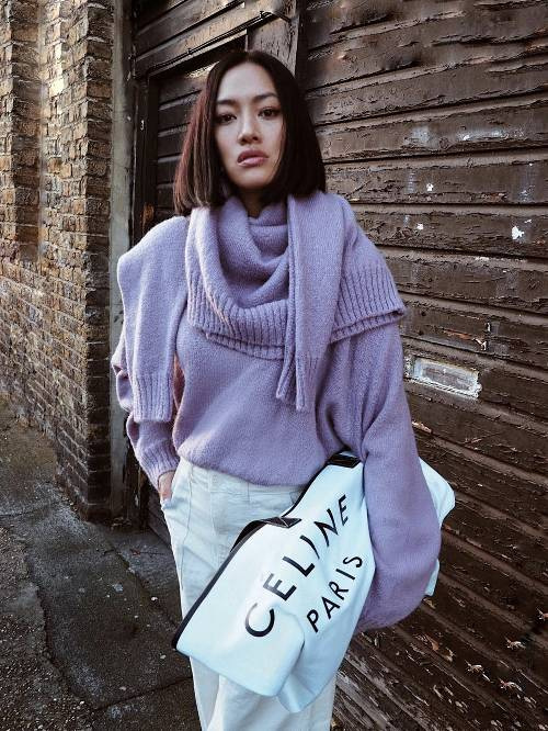 an oversized lilac sweater, a matching scarf, a white midi skirt and a large clutch bag