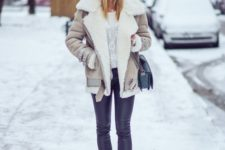 16 black leather leggings, black boots, a printed sweater and a neutral shearling coat plus a black beanie