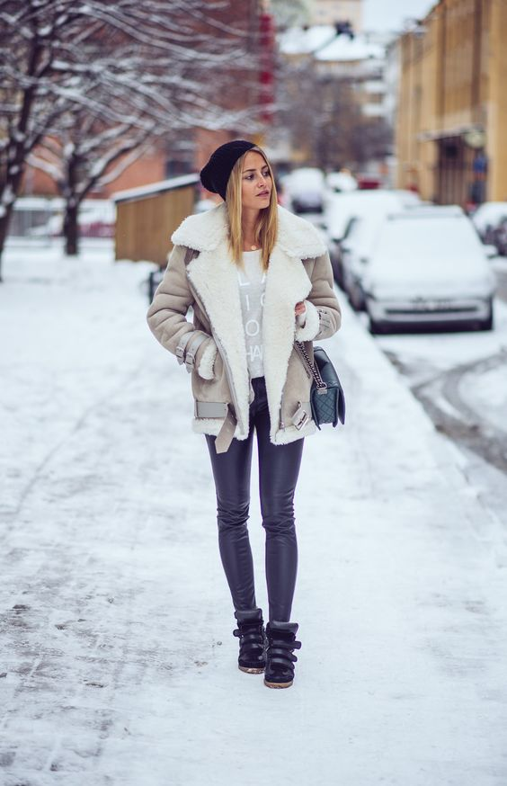 black leather leggings, black boots, a printed sweater and a neutral shearling coat plus a black beanie