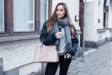 16 tan combat boots, black skinnies, a grey sweater, a black puffed coat and a blush bag