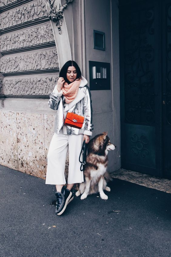 white culottes, a pink scarf, a silver shearling coat, a red bag and black pltform boots