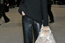 Olivia Palermo wearing cropped black leather pants, a black sweater, a faux fur waistcoat and snake print shoes