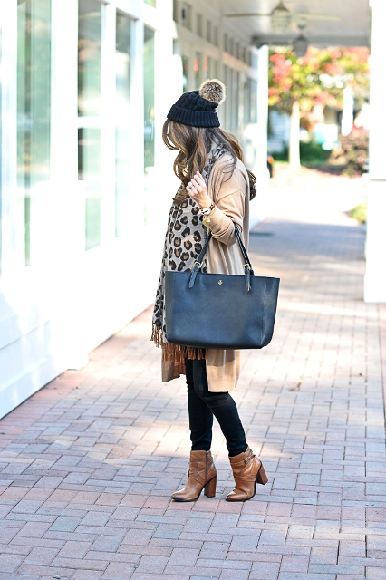 With beige cardigan, black pants, brown boots, tote and leopard scarf