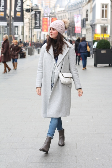 With beige coat, white bag, jeans and gray ankle boots