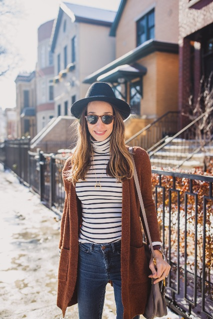 With black hat, brown cardigan, jeans and beige bag