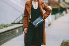 With black jumpsuit, fur coat, crossbody bag and red ankle boots