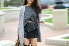 With black leather mini skirt, gray shirt, light gray cardigan and lace up over the knee boots