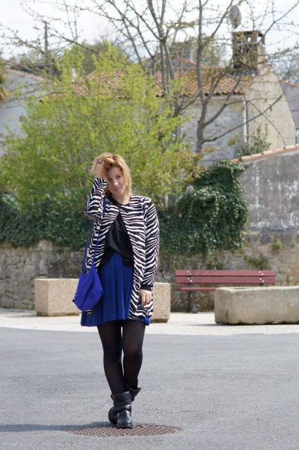 With black loose shirt, blue mini skirt, blue bag and boots