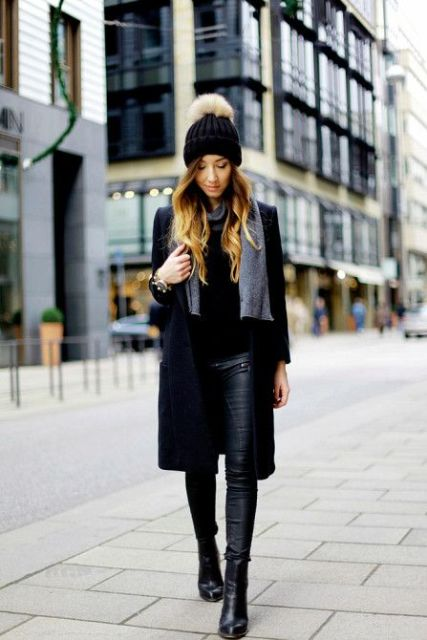 With black shirt, black knee length coat, leather pants, boots and gray scarf
