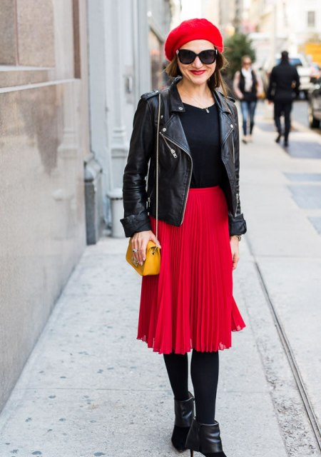 With black shirt, black leather jacket, yellow bag, pleated skirt and black ankle boots