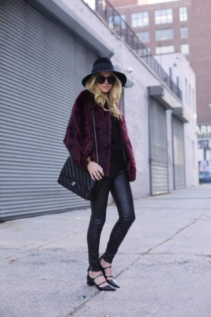 With black shirt, black leather pants, wide brim hat, chain strap bag and shoes