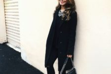 With black shirt, black skinny pants, knee-length coat and chain strap bag