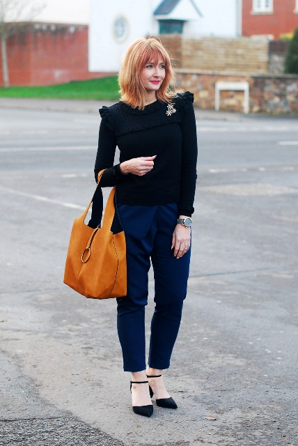 With black shirt, blue trousers and black shoes