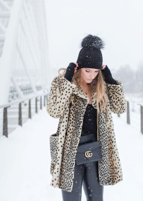 With black shirt, leopard coat, chain strap bag and black leather pants