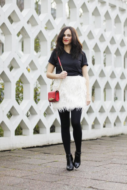 With black t-shirt, red mini bag, black tights and black ankle boots