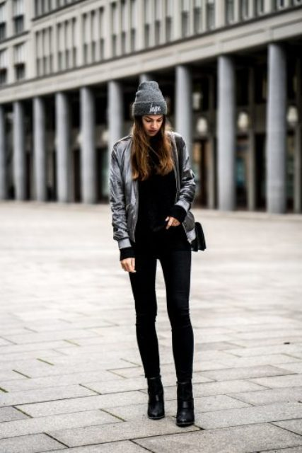 With black turtleneck, black pants, heeled boots, gray hat and small bag