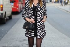 With black wide brim hat, black mini dress, ankle boots and chain strap bag