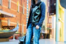 With blue shirt, patent leather vest, cuffed jeans, yellow and black high heels and sunglasses
