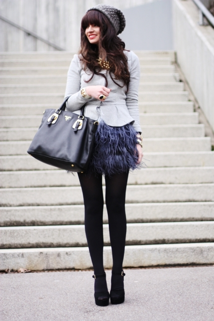 With gray jacket, hat, black tights, platform shoes and black tote