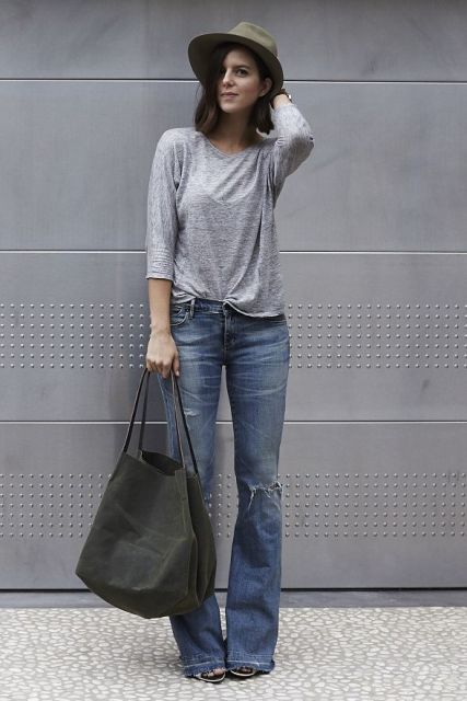 With gray shirt, distressed jeans, hat and high heels