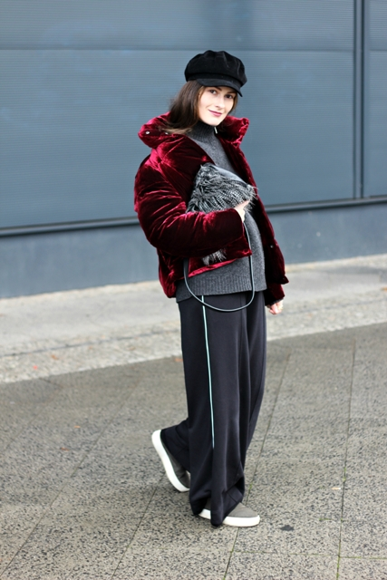 With gray sweater, black cap, fur clutch, wide leg pants and slip on shoes