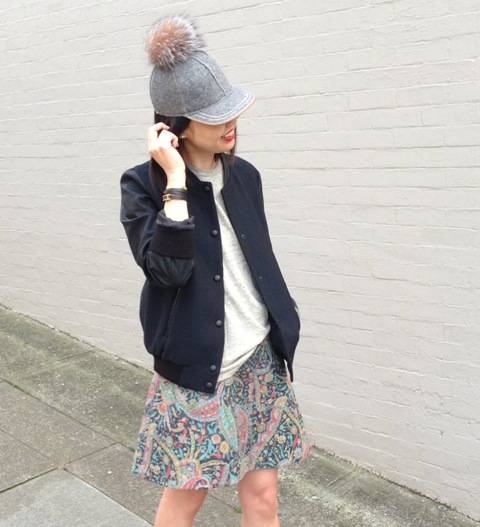 With gray t shirt, navy blue jacket and printed skirt