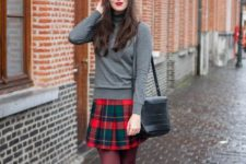 With gray turtleneck, plaid skirt, black leather bag and black boots