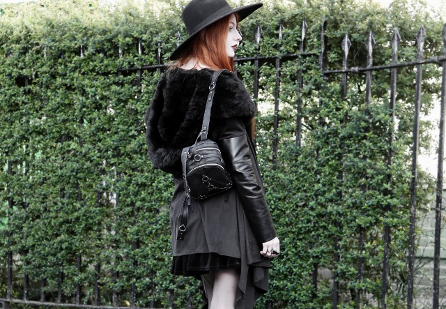 With leather and fur jacket, black skirt and black wide brim hat