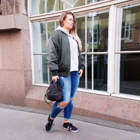 With light gray hoodie, distressed jeans, black and white sneakers and gray bomber jacket