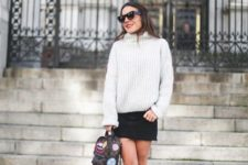 With loose sweater, black mini skirt and printed ankle boots