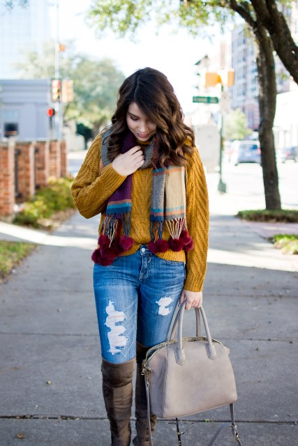 With loose sweater, distressed jeans, beige bag and high boots