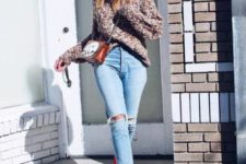 With loose sweater, distressed jeans, chain strap bag and red sock boots
