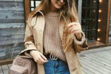 With loose sweater, trench coat, high-waisted jeans and belt