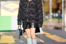 With oversized jacket, black leather skirt and round bag