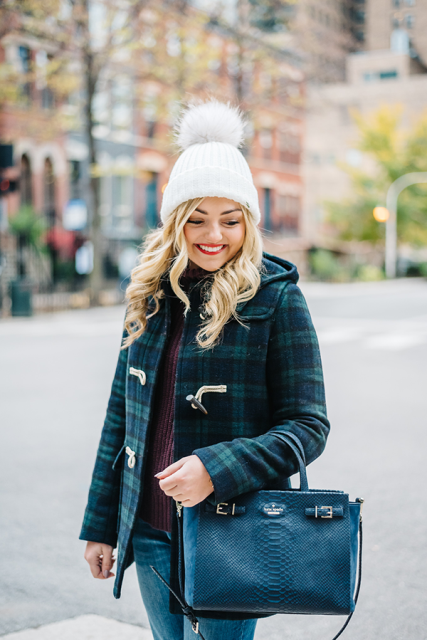 With plaid jacket, jeans and black leather bag