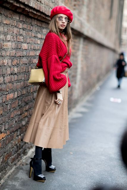 With red loose sweater, beige leather skirt, high heels and small bag