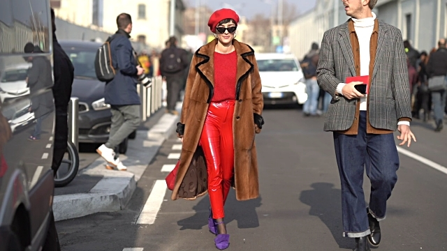 With red shirt, red leather trousers, purple shoes and brown coat