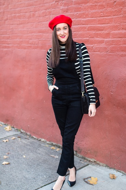 With striped shirt, black jumpsuit, black shoes and leather bag