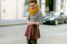 With striped shirt, leather mini skirt, lace up boots and bag