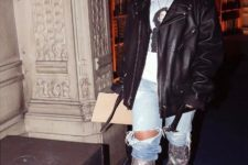 With t-shirt, black leather jacket, clutch and distressed jeans