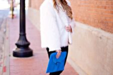 With white shirt, black skinny pants, ankle boots and blue clutch